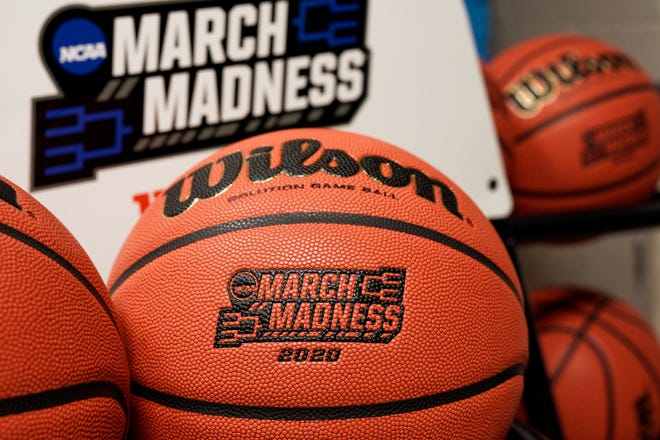 FILE - In this March 16, 2020, file photo, official March Madness 2020 tournament basketballs are displayed in a storeroom at the CHI Health Center Arena, in Omaha, Neb. The dominos started tumbling in March, when the NCAA abruptly called off March Madness, given no choice but to forgo a nearly $800 million TV payment that helps keep the entire college sports machine running. (AP Photo/Nati Harnik, File)
