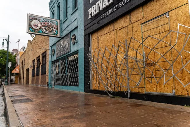 Workers boarded up bars on Sixth Street in Austin after Gov. Greg Abbott closed bars for a second time in June. After a financially devastating year, out-of-work Texans were dealt another blow this week when a congressional coronavirus relief package's fate became uncertain after President Donald Trump threatened to veto it.
