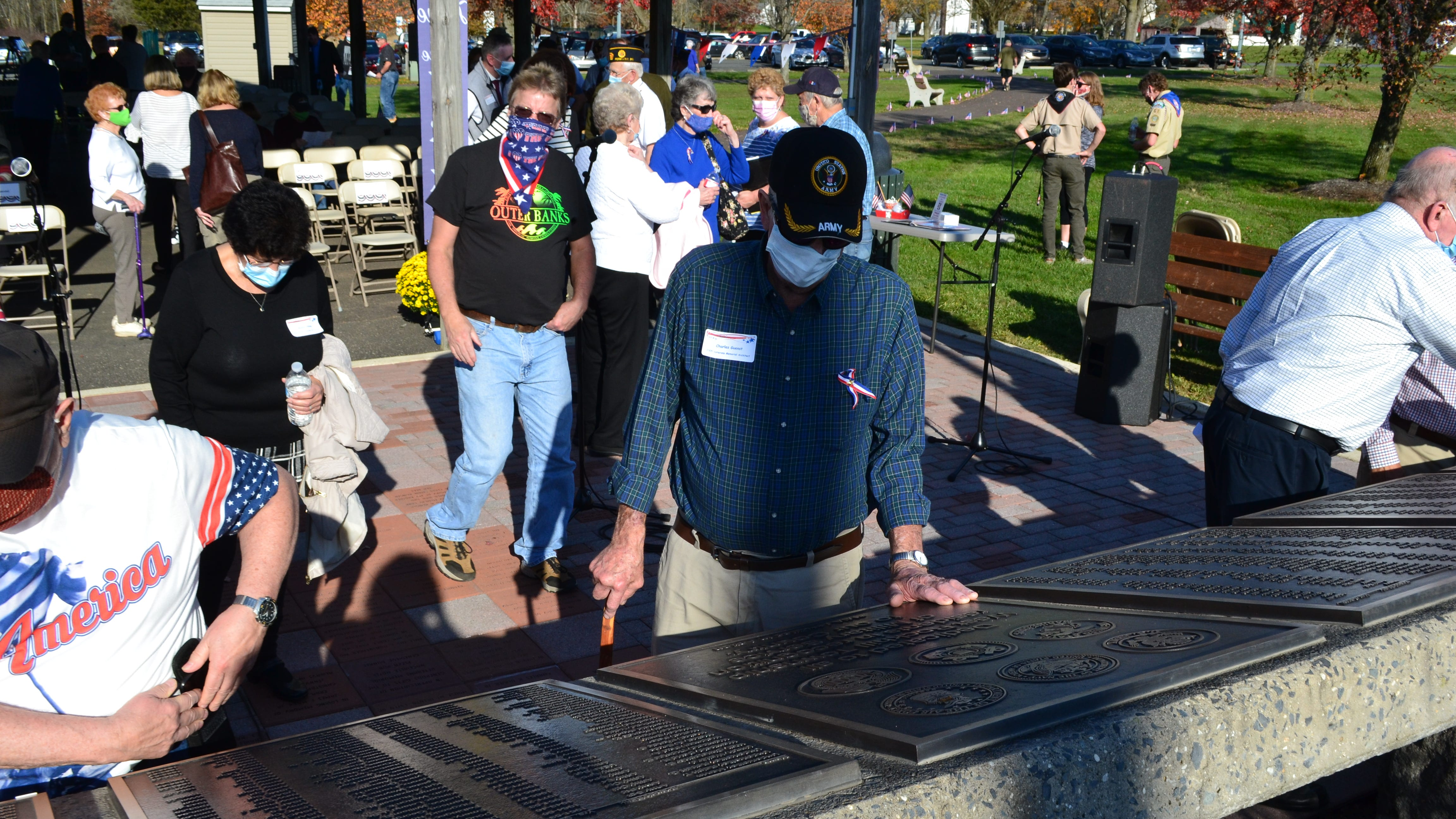 West Rockhill resident and Army Veteran Charlie Guenst  (center) looks over one of the plaques at the township's veterans memorial on Nov. 8. Guenst, who died on Dec. 13, was responsible for creating the original 391-name memorial in 2005.
