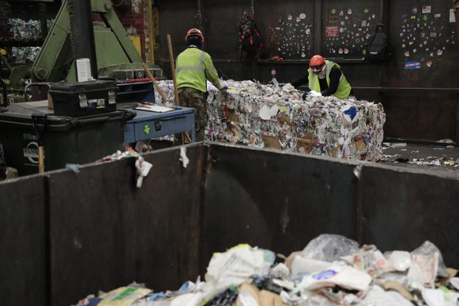 Workers pull plastic from bales of recyclables at Rumpke of Ohio in Columbus on Dec. 24. The Columbus City Council is scheduled to vote Monday on paying $9.54 million to Rumpke in the final year of a five-year contract to collect recyclables and yard waste from the city's residents.