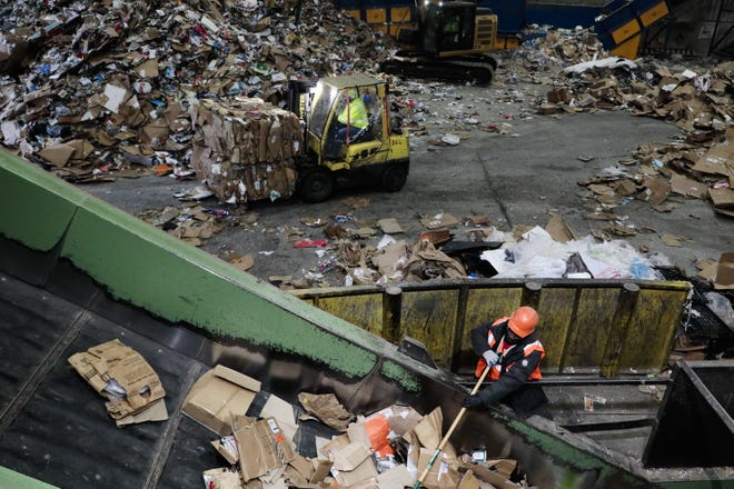 A Rumpke employee sorts cardboard on Thursday, Dec. 24, 2020 at Rumpke in Columbus, Ohio. Americans throw away roughly 25% more trash during the holiday period between Thanksgiving and New Year's Day than any other time of year.