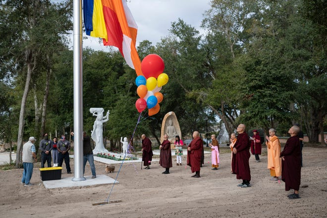 People watch as the Buddist flag is raised at the Đại Niệm Xứ Thiền Viện. Satipatthana Meditation Center in Leesburg.