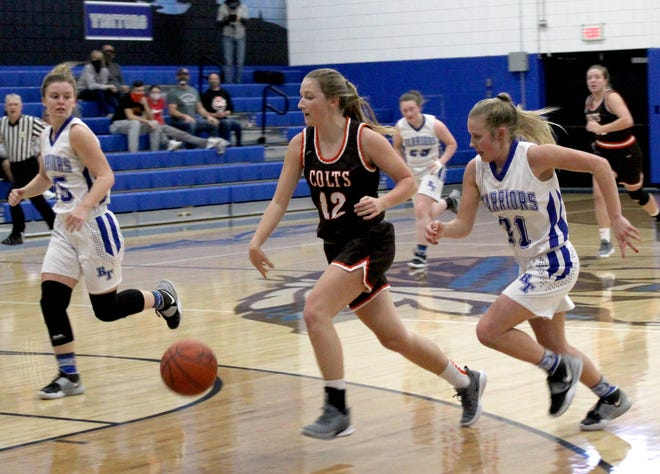 Meadowbrook senior Laney Bell (12) heads up-court past Buckeye Trail defenders Brooke Baird (35) and Abby Wayble (31) during action Wednesday evening at Buckeye Trail High School.