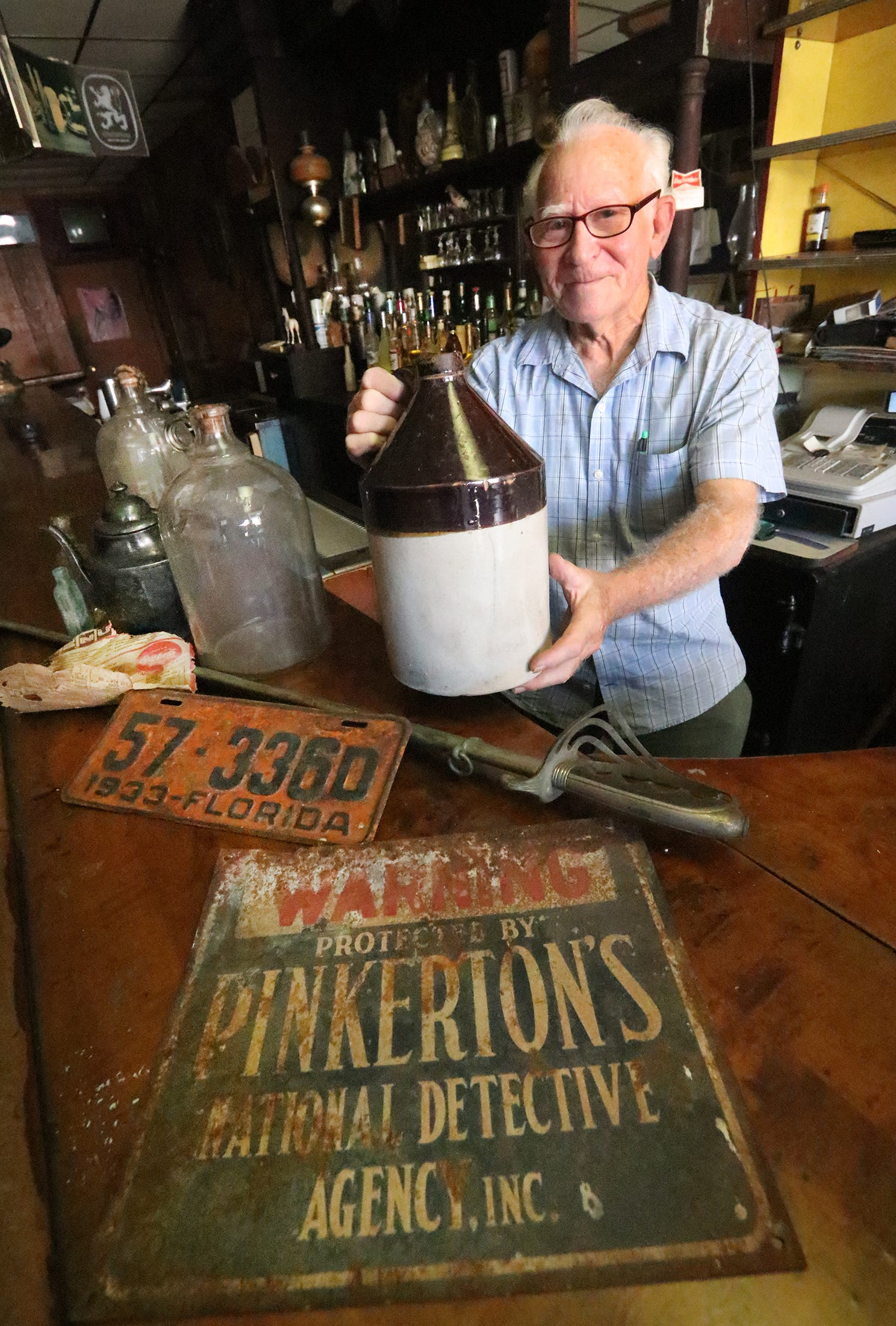Warren Trager, longtime owner of a Mary McLeod Bethune Boulevard bar, holds an old whiskey jug he found in the 100-year-old tavern. It's one of many artifacts he has found under floors, inside walls and within hidden rooms. He has also discovered a 1933 license plate, sword, silver tea pot and bag of cash.