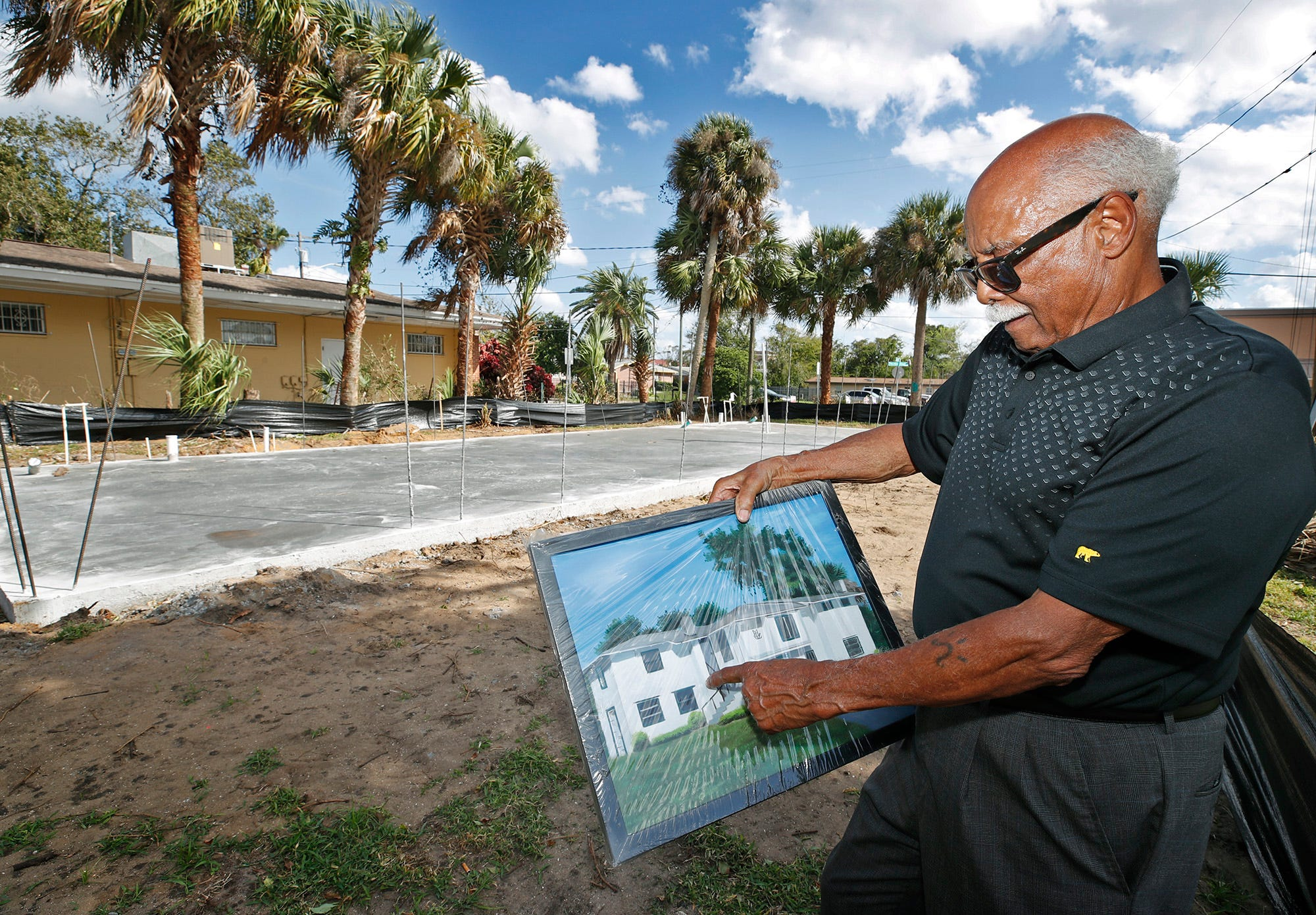 Harold Lucas shows a picture of the home he was born and raised in. He's shown standing on the site of the home located at the northeast corner of Mary McLeod Bethune Boulevard and Jefferson Street. He had the home demolished after someone drove their car into it. He's now building a structure that will house his personal mementos and memorabilia of Mary McLeod Bethune, and provide meeting space.