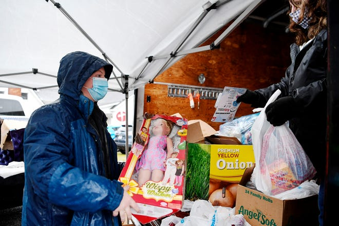 Landon Maybin, left, collects toys to give to a family with help from Rena Bowen at Mark White and Associates office on Christmas Eve during a toy giveaway sponsored by WHKP, Mark White and Associates, Mike Gilliam Insurance and Bay Breeze Restaurant.