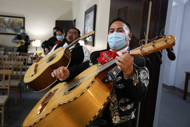 Enrique Leon plays guitarron and sings during the funeral service for his friend and fellow musician, Florentino Chavez, at Martinez Funeral Home, Dec. 4, 2020, in Chicago. Leon is the leader of Mariachi Mexico Vivo.    (Stacey Wescott / Chicago Tribune/TNS)