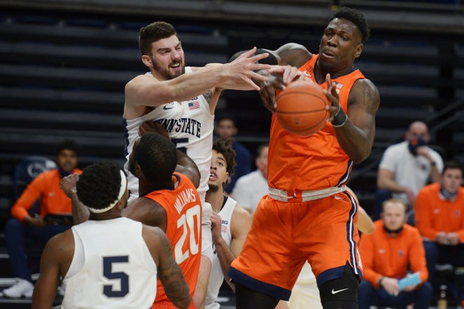 Penn State's Trent Buttrick (15) and Illinois' Kofi Cockburn vie for a rebound during the second half of an NCAA college basketball game Wednesday, Dec. 23, 2020, in State College, Pa. (AP Photo/Gary M. Baranec)