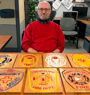 Robert Davet Sr. with some of the plaques he painted. The images are the patches the Twinsburg Fire Department used.