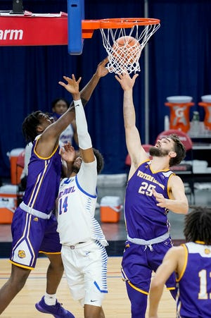 Western Illinois' Tamell Pearson, left, and Will Carius (25) battle DePaul's Nick Ongenda for a rebound during the second half of an NCAA college basketball game Wednesday, Dec. 23, 2020, in Chicago. [AP Photo/Charles Rex Arbogast]