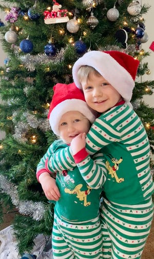 Christmas has come and Benson Freese, 3, hugs little sister Madison, 2, by the Christmas tree because they are having a happy holiday. They are children of Caleb and Alyssa Freese.