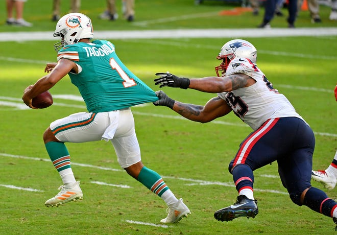 Dolphins quarterback Tua Tagovailoa tries to get away from Patriots defensive tackle Byron Cowart during last Sunday's game at Hard Rock Stadium.