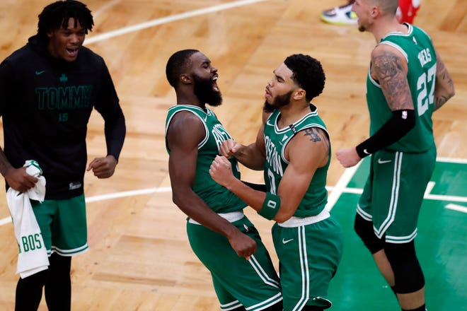 The Celtics' Jayson Tatum (0) celebrates with Jaylen Brown (7) after making the go-ahead basket with less than a second on the clock during the second half of  Wednesday's season opener against the Milwaukee Buck in Boston's TD Garden.