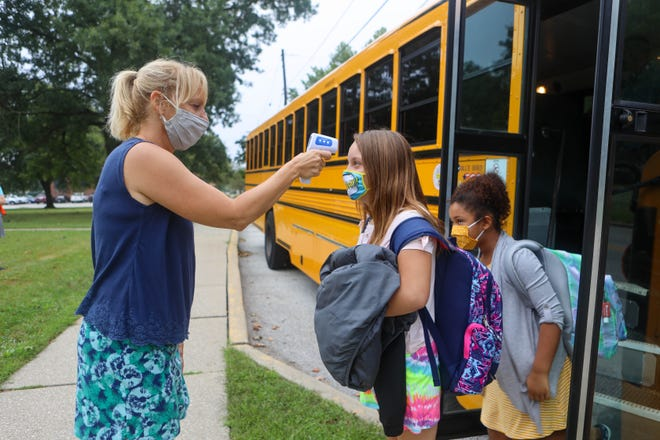 Holden Elementary School teacher Christi Bates checks the temperature of kids as they file off the school bus on the first day of school in Kent.