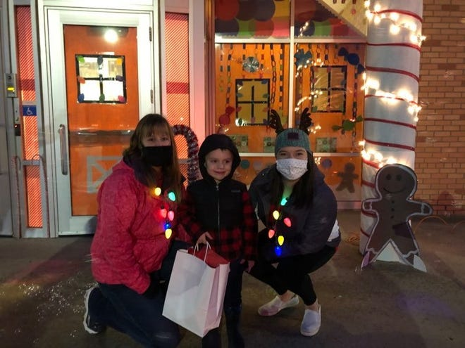 Kara Kuehn (left), Early Childhood coordinator, and Maria Piette, Cardinal Kids Club coordinator/Discovery Time teacher, greet families as they came to pick up gingerbread house kits Thursday evening.