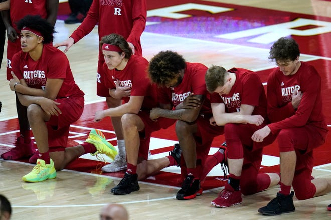 Members of the Rutgers men's basketball team take a knee during the playing of the national anthem prior to a game against Maryland in College Park, Md. on Dec. 14. The coronavirus, combined with the harsh spotlight that shined on racial inequality in the United States, further exposed the exploitative side of a system that relies heavily on Black football and basketball players to bring in the bucks.