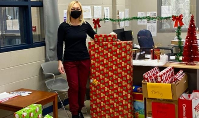 Kelly Melo, a NBPS school nurse, stands with some of the many gifts ready to go to families of Keith Middle School students. The donated presents are part of NBPS 'Christmas is for Kids' project, which aims to ensure families have gifts for their children to open this holiday season.