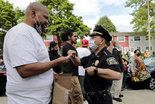New Bedford Police Chief Joseph Cordeiro offers his card to a protester, during a protest this summer in New Bedford. The Chief announced the city would rescind a controversial policy Thursday, while Mayor Jon Mitchell announced that recommendations from the Commission on the Police Use of Force would be implemented.
