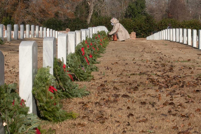 A woman sets a wreath at a veteran's grave at New Bern National Cemetery. More than 5,000 wreaths remain at the cemetery through Jan. 23.