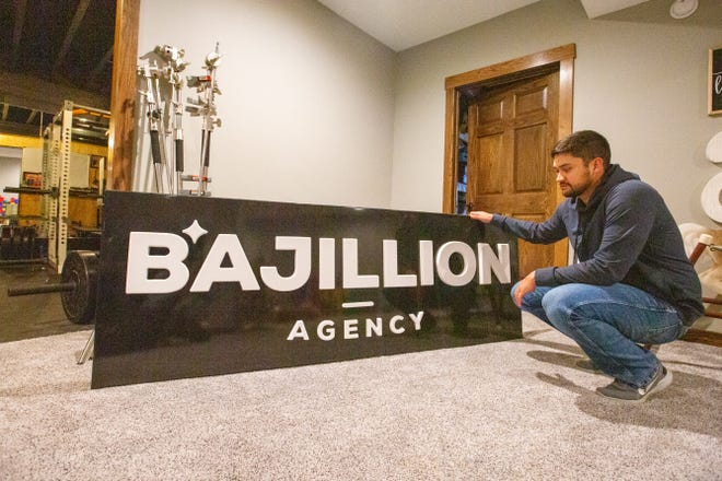 Austin Abbott pulls a Bajillion Agency sign out in his basement Wednesday afternoon. Abbott Unlimited recently acquired Bajillion Agency and Motovike Films earlier this month.