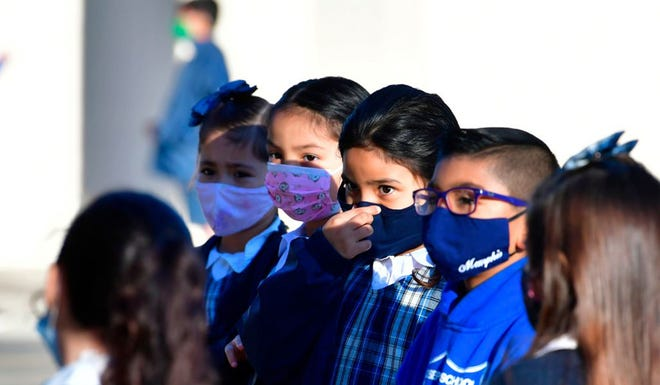 A students adjusts her facemask at St. Joseph Catholic School in La Puente, California in November.