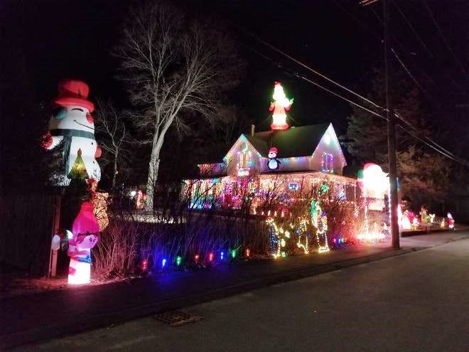A 33-foot-tall snowman, at left, towers over the Christmas lights scene at the home of Charles and Meg Bear and family at 46 Cherry St. The Bears love sharing the festive light sight with all the area families who are driving by this season.
