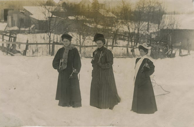 The skates the women carry are of the strap-on variety, dating the photograph to the 1910s or 1920s.