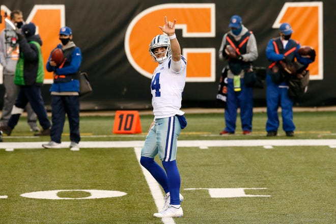 Dallas Cowboys quarterback Andy Dalton (14) signs up to his family after throwing a touchdown to seal the game in the fourth quarter of the NFL Week 14 game between the Cincinnati Bengals and the Dallas Cowboys at Paul Brown Stadium in downtown Cincinnati on   Sunday, Dec. 13, 2020. Former Bengals quarterback Andy Dalton led the Cowboys to a 30-7 over the Bengals.