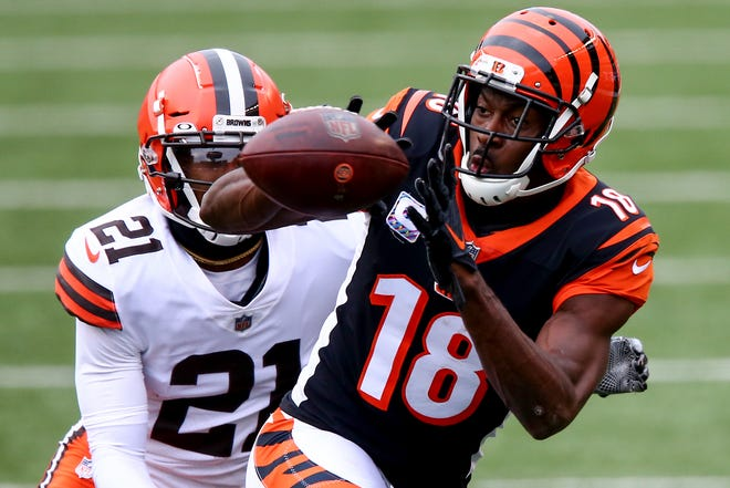 Cincinnati Bengals wide receiver A.J. Green (18) catches a pass as Cleveland Browns cornerback Denzel Ward (21) defends during the fourth quarter of a Week 7 NFL football game, Sunday, Oct. 25, 2020, at Paul Brown Stadium in Cincinnati. The Cleveland Browns won 37-34.