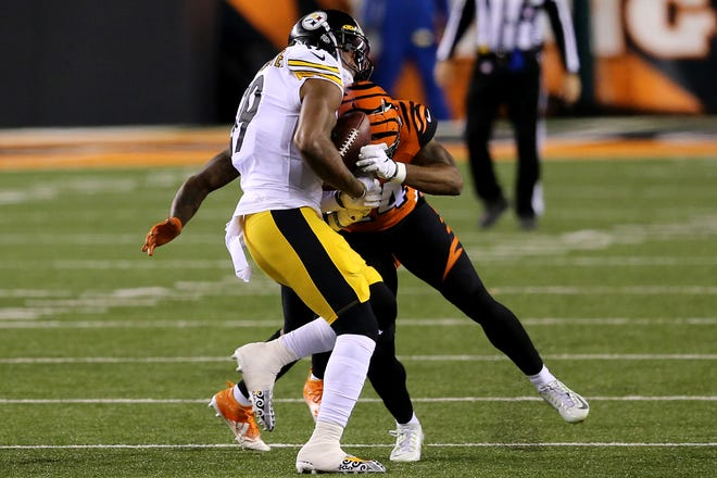 Cincinnati Bengals strong safety Vonn Bell (24) forces a fumble of Pittsburgh Steelers wide receiver JuJu Smith-Schuster (19) in the first quarter during an NFL Week 15 football game, Monday, Dec. 21, 2020, at Paul Brown Stadium in Cincinnati.