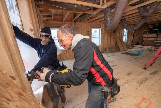 Joel Morandini, left, and Tom Wencel cut out a window as they work on an addition of a second level to Wencel's home on Tulane Street in Dearborn Heights, Dec. 24, 2020.