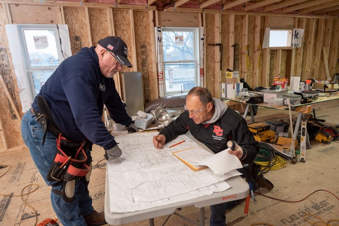 Dave Rushing, left, and Tom Wencellook over blueprints as they work on an addition of a second level toWencel'shome on Tulane Street in Dearborn Heights, Dec. 24, 2020. Dozens of volunteersare helpingWencel and his wife, Debbie, with the expansion which willaddroom for the couple's fiveyoung grandchildren, whom they'vefostered since their 36-year-old daughter, Jaime Wencel, died of a heart attack on July 11, 2017.