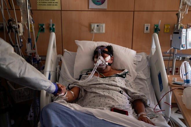 Pasien COVID-19 Efrain Molina, tengah, mendapat pukulan dari kepala perawat Edgar Ramirez di Providence Holy Cross Medical Center di bagian Mission Hills di Los Angeles, Selasa.