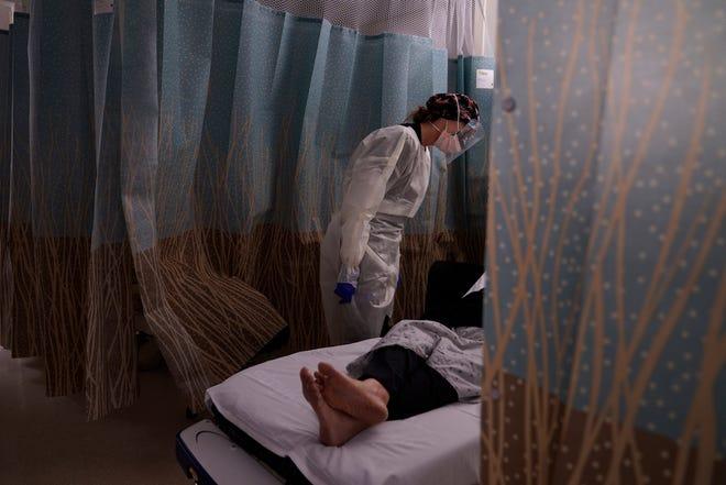 Perawat terdaftar Jennifer Henderson berbicara dengan pasien yang menunjukkan gejala virus corona di ruang gawat darurat di Providence Holy Cross Medical Center di bagian Mission Hills Los Angeles, Selasa.
