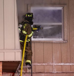 A Fond du Lac Fire/Rescue Department member sprays water into an apartment on fire Wednesday, December 23, 2020 at the Maplewood Commons apartment complex on Martin Avenue in Fond du Lac, Wis. Doug Raflik/USA TODAY NETWORK-Wisconsin