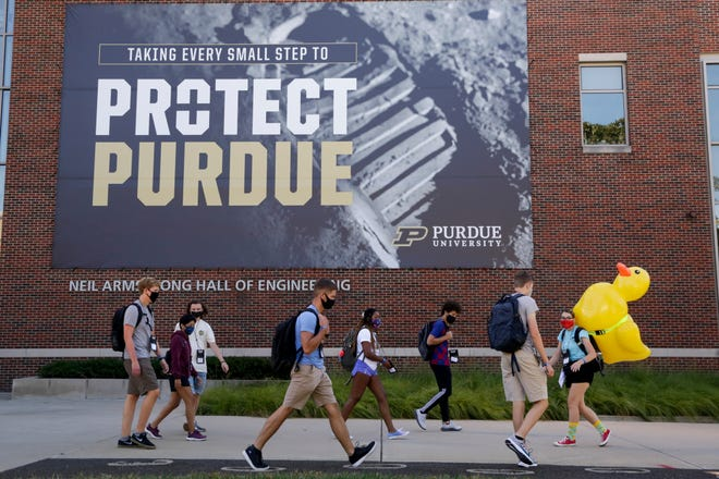 A group of students walks past the Neil Armstrong Hall of Engineering at Purdue University, Wednesday, Aug. 19, 2020 in West Lafayette.