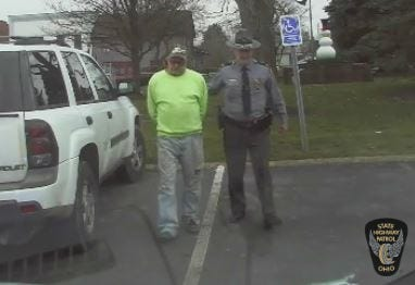Gary Papst is escorted by Staff Lt. Michael Vinson of the Bucyrus Patrol Headquarters in this photo taken off a patrol video by the Ohio Highway Patrol.
