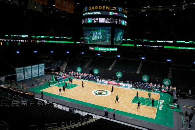 Bucks and Celtics players warm up in an empty TD Garden in Boston before the teams officially tipped off their seasons.