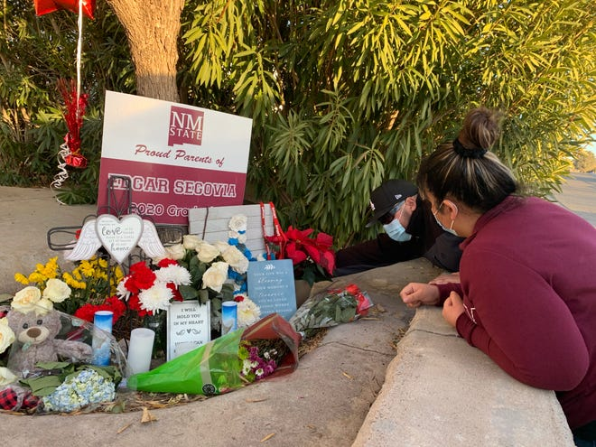 Jaime and Denise Segovia organize items left at a memorial outside the home their parents shared with their little brother Edgar Segovia, who was shot and killed in Las Cruces on Saturday, Dec. 19, 2020.