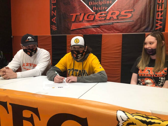 Aztec's Sammy Minton signs his National Letter of Intent on Wednesday, Dec. 23, 2020, to continue his wrestling career at NAIA's Ottawa University.