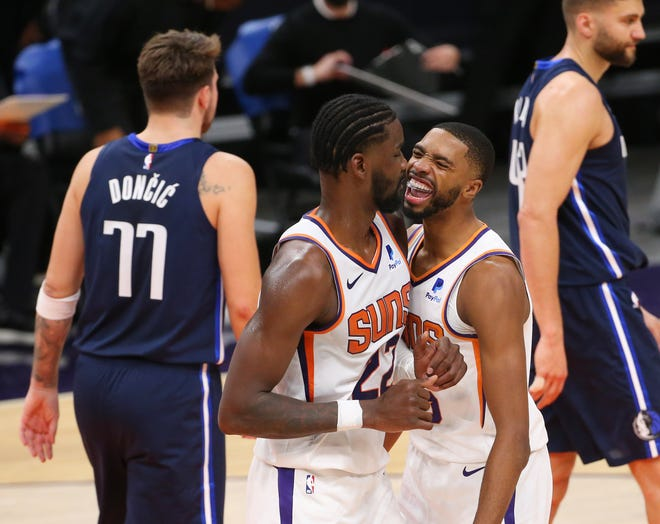 Phoenix Suns center Deandre Ayton (22) and forward Mikal Bridges (25) celebrate their 106-102 victory against the Dallas Mavericks at Talking Stick Resort Arena in Phoenix Dec. 23, 2020.
