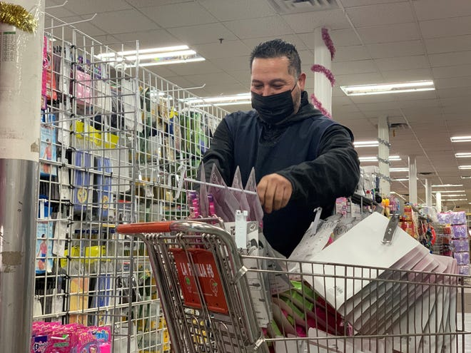 Ivan Caballero, an employee at La Familia store in downtown Nogales, places toys into a shopping cart to take to the main store. He was out of work for seven months when the store closed, but work has been very slow and he fears they will have to shut down again.
