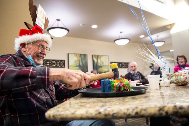 Woody Campbell uses a mallet to break open a miniature piñata during his 100th birthday celebration on Wednesday at Bonaventure Senior Living in Salem.
