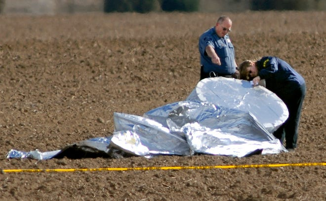 An investigator, right, with the National Transportation Safety Board and an unidentified police officer inspect the scene where a balloon landed in a field southeast of Hudson, Colo., on Thursday, Oct. 15, 2009. The homemade balloon aircraft floated away from a yard in Fort Collins after a 6-year-old boy was reported seen climbing in, setting off a frantic scramble by the military and law enforcement before the balloon slowly touched without the boy inside. The boy was later found in the attic of his home.