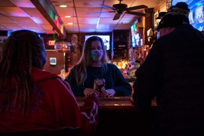 Bartender Genevieve Gilson chats with customers Suzette King, left, and Andrew Taylor inside Bier Stube off of North High Street on Christmas Eve. Bier Stube is prepared to host socially distanced New Year's Eve patrons this year.