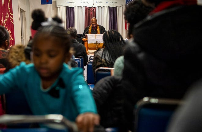 Love-Lea Towns, 5, turns in her chair while her father, L.B. Towns Sr., preaches to an enthusiastic congregation at People After True Holiness church in Columbus.