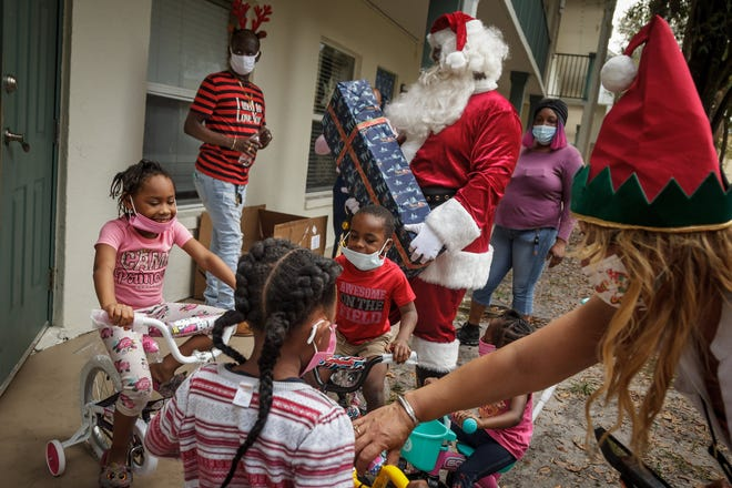 Volunteers help distribute gifts to families at Azure Estates in Riviera Beach, on Thursday, December 24, 2020. Nearly $20,000 of gifts were purchased by Secret Santas of Tiara, a group of residents of the condominium on Singer Island. Children wrote gift wish lists for Santa and the organization aimed to purchase a gift for every child aged 13 and under in the complex.