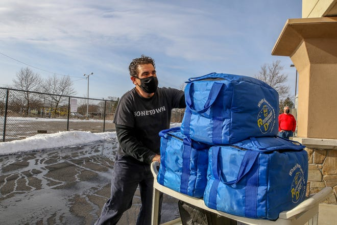 Shane Caledonia, owner of Bonetown Burgers and BBQ, delivers meals on Christmas Eve to homeless people recovering from COVID-19 at the state's quarantine and isolation site in Warwick.