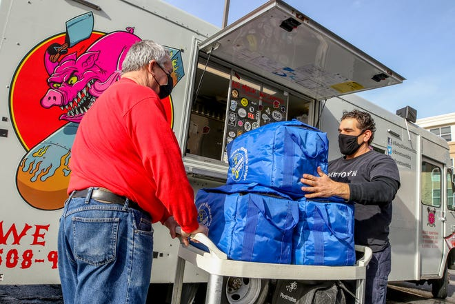 Steve Gilman, left, owner of Poppy's Waffles, helps Shane Caledonia, owner of Bonetown Burgers and BBQ, deliver meals on Christmas Eve to homeless people recovering at the state quarantine and isolation site in Warwick.