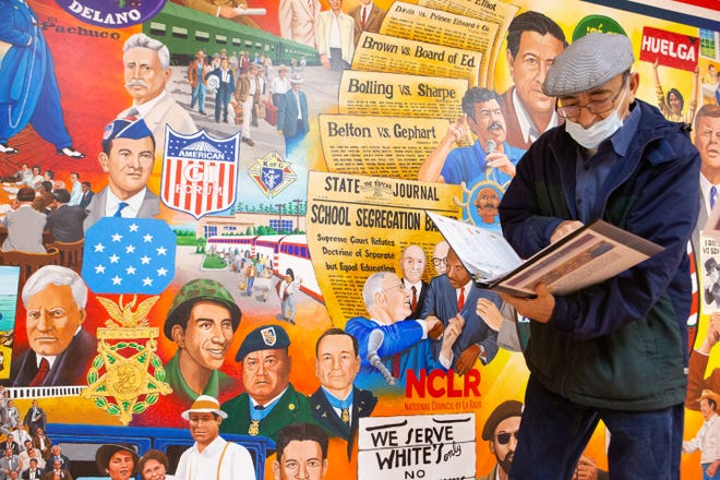 """Andy Valdivia flips through a binder full of notes on each individual subject on his newest mural """"Our History: Lucha por Derechos Civiles,"""" which translates to fight for civil rights, on Dec. 18 in the basement of the Marlo Cuevas-Balandran Activity Center, 224 N.E. Branner St."""